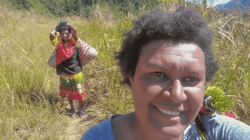Martha Wame on top of a mountain on her way to rural wards.