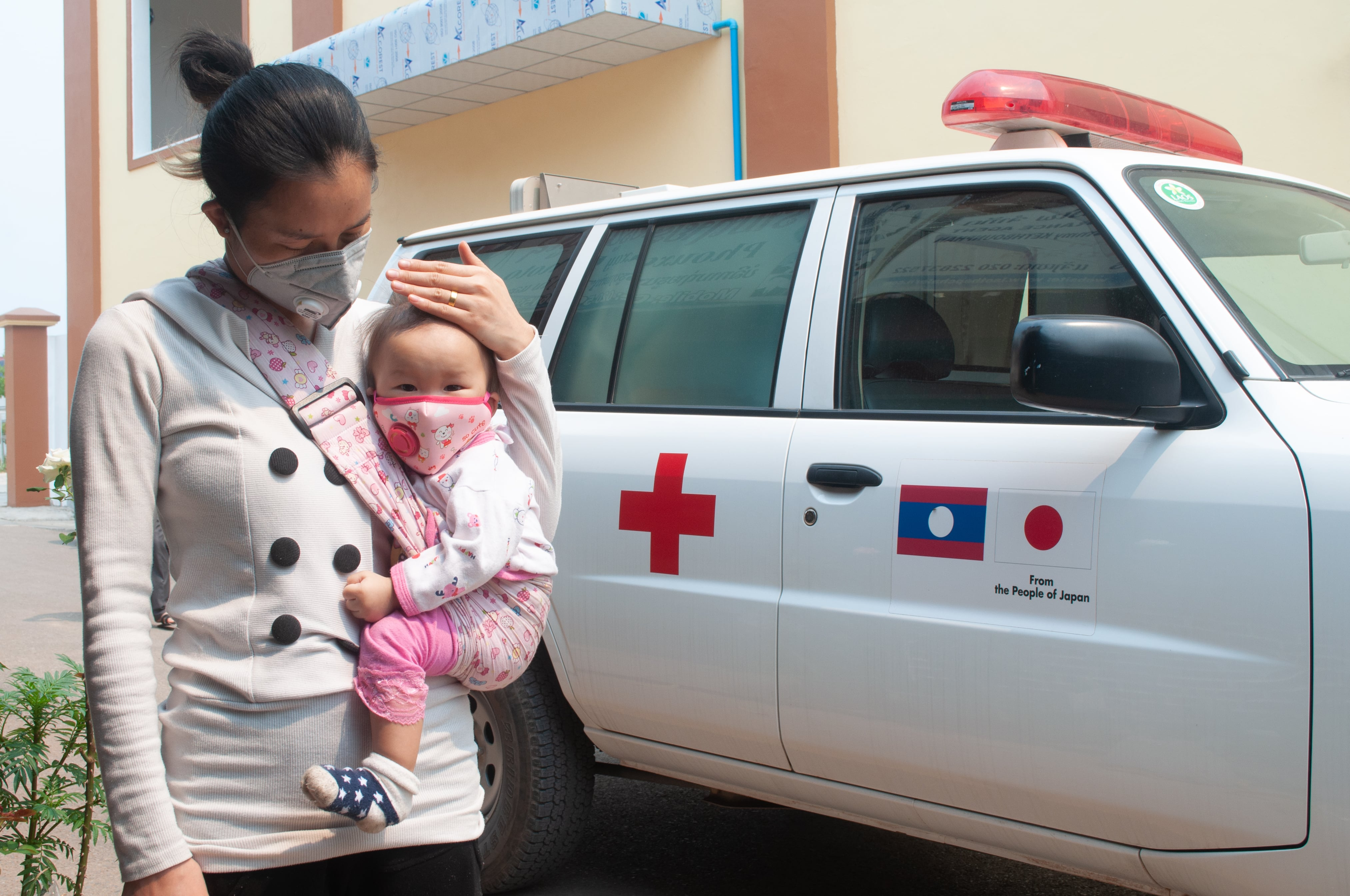 A woman and her baby wait for a COVID-19 test in Oudomxay Province, Lao PDR