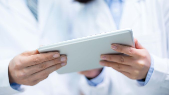 Two medical professionals use a tablet to analyse data